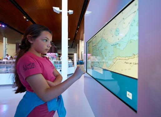 une jeune fille devant une borne numérique à la cité de la voile